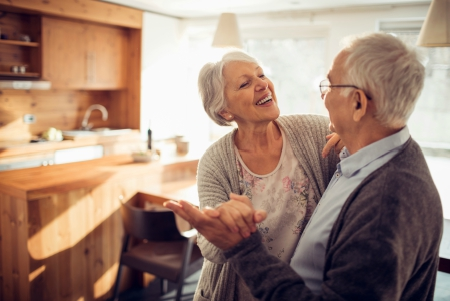 Elderly couple holding hands smiling in a kitchen